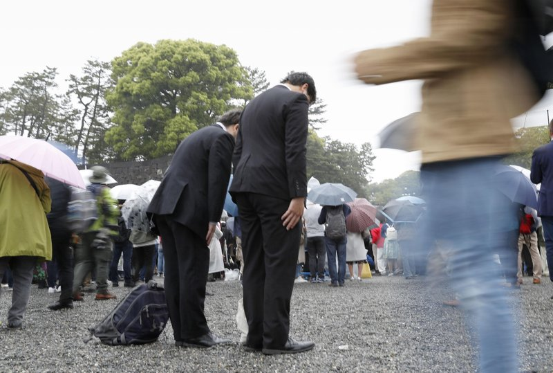 People bow toward the Imperial Palace as Emperor Akihito's abdication ceremony is held in Tokyo Tuesday, April 30, 2019. Emperor Akihito announced his abdication at the palace ceremony Tuesday in his final address, as the nation embraced the end of his reign with reminiscence and hope for a new era. (Shinji Kita/Kyodo News via AP)