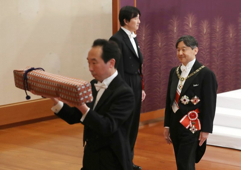 Japan's new Emperor Naruhito, right, leaves after the ceremony to receive the Imperial regalia of sword and jewel as proof of succession at Imperial Palace in Tokyo, Wednesday, May 1, 2019. Standing at back is Crown Prince Akishino. (Japan Pool via AP)