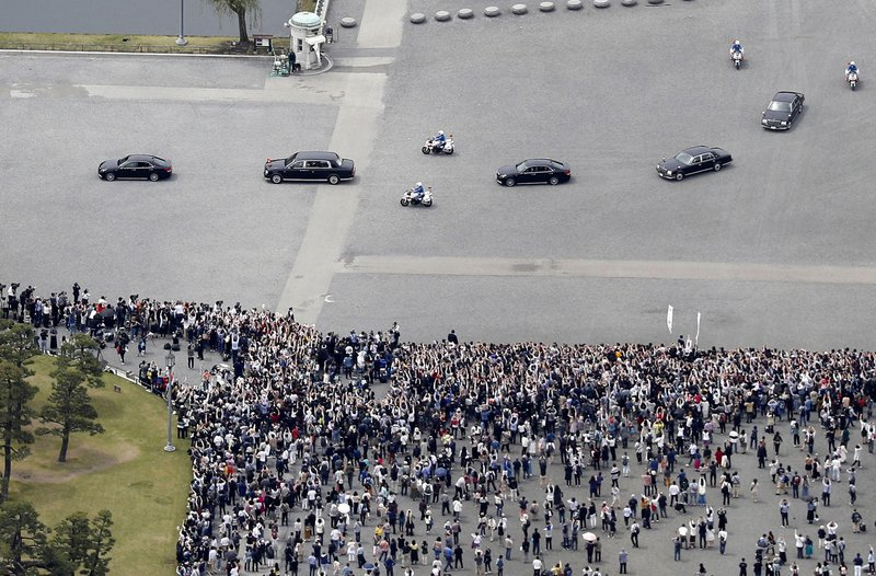 In this aerial photo, the motorcade of Japan's new Emperor Naruhito, second from left, move past well-wishers after attending his imperial rituals at the Imperial Palace Wednesday, May 1, 2019, in Tokyo. Emperor Naruhito inherited Imperial regalia and seals as proof of his succession and pledged in his first public address Wednesday to follow his father's example in devoting himself to peace and staying close to the people. (Takuya Inaba/Kyodo News via AP)