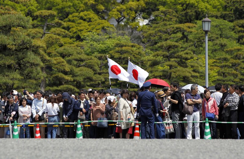 People gather around the Imperial Palace where Crown Prince Naruhito is to be enthroned to become new Japanese Emperor Wednesday, May 1, 2019, in Tokyo. Japan has new Emperor Naruhito to perform his first ritual after succeeding the Chrysanthemum Throne from his father Akihito who abdicated the night before. (AP Photo/Eugene Hoshiko)
