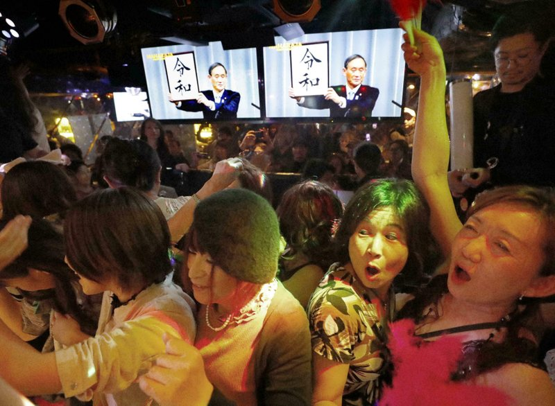 People celebrate as the countdown to new Emperor Naruhito's era of Reiwa, start, a few minutes before Wednesday, May 1, 2019, in Tokyo, Japan. Emperor Akihito announced his abdication at a palace ceremony Tuesday in his final address. The screens, rear, shows that Japan's Chief Cabinet Secretary Yoshihide Suga unveiled the name of new era