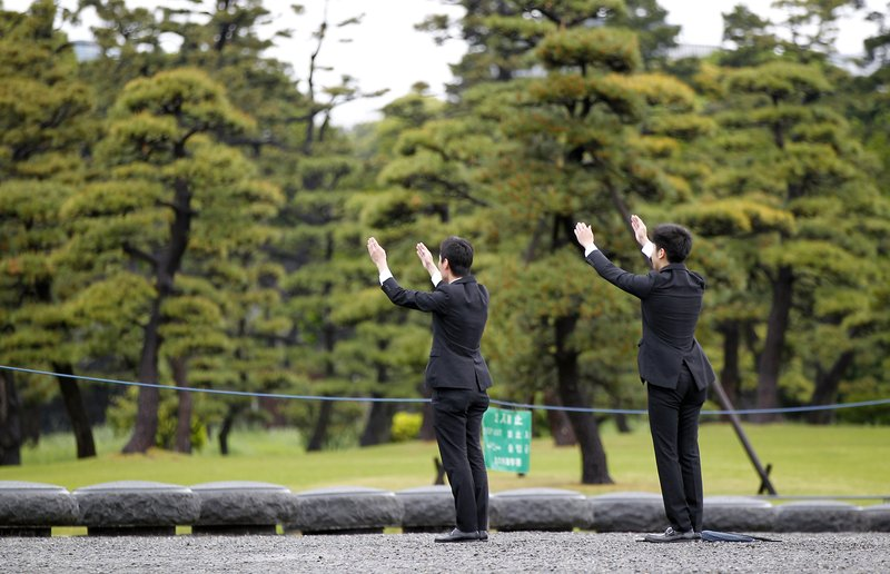 People raise their arms in the air toward Imperial Palace in Tokyo Wednesday, May 1, 2019. Japan has new Emperor Naruhito and he will perform his first ritual hours after succeeding the Chrysanthemum Throne from his father Akihito who abdicated the night before. (AP Photo/Eugene Hoshiko)