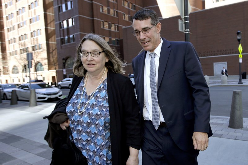 FILE - In this April 24, 2019 file photo Michael Center, right, former men's tennis coach at the University of Texas at Austin, departs federal court with an unidentified woman after he pled guilty to charges in a nationwide college admissions bribery scandal. Since dozens of wealthy parents and coaches at elite universities were arrested in March, two parents and two coaches, including Center, have agreed to cooperate with authorities. (AP Photo/Steven Senne, File)