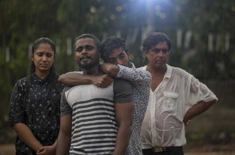 """FILE -  In this April 22, 2019 file photo, mourners grieve at the burial of three members of the same family victims of an Easter Sunday bomb blast at St. Sebastian Church in Negombo, Sri Lanka. In a video released on April 29, the Islamic State group's leader extolled militants in Sri Lanka for """"striking the homes of the crusaders in their Easter, in vengeance for their brothers in Baghouz,"""" a reference to IS' last bastion in eastern Syria, which was captured by U.S.-backed fighters in March. (AP Photo/Gemunu Amarasinghe, File)"""
