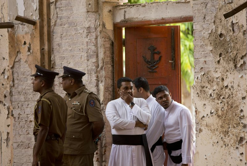 """FILE - In this April 22, 2019, file photo, clergymen visit the scene of a suicide bombing at St. Sebastian Church in Negombo, Sri Lanka. In a video released on April 29, the Islamic State group's leader extolled militants in Sri Lanka for """"striking the homes of the crusaders in their Easter, in vengeance for their brothers in Baghouz,"""" a reference to IS' last bastion in eastern Syria, which was captured by U.S.-backed fighters in March. (AP Photo/Gemunu Amarasinghe, File)"""