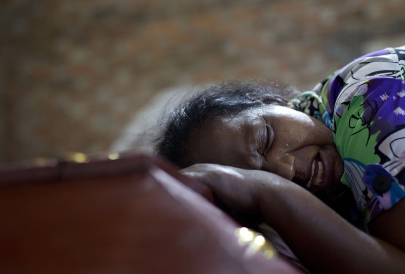 """FILE - In this April 22, 2019 file, photo, Lalitha weeps on the coffin with the remains of 12-year old niece, Sneha Savindi, who was a victim of Easter Sunday bombing at St. Sebastian Church in Negombo, Sri Lanka. In a video released on April 29, the Islamic State group's leader extolled militants in Sri Lanka for """"striking the homes of the crusaders in their Easter, in vengeance for their brothers in Baghouz,"""" a reference to IS' last bastion in eastern Syria, which was captured by U.S.-backed fighters in March. (AP Photo/Gemunu Amarasinghe, File)"""