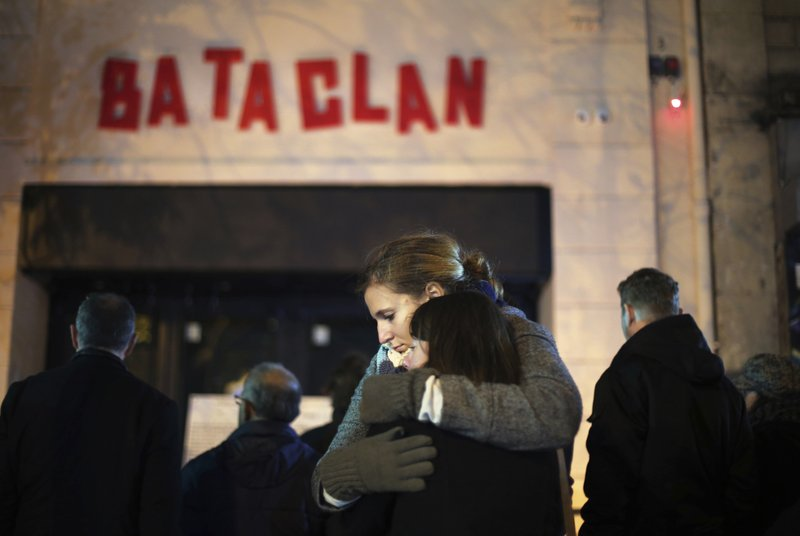 FILE -  In this Nov. 13, 2016 file photo, women hug in front of the Bataclan concert hall in Paris, as France marked the anniversary of Islamic extremists' coordinated attacks on Paris with a somber silence that was broken only by voices reciting the names of the 130 slain. (AP Photo/Thibault Camus, File)