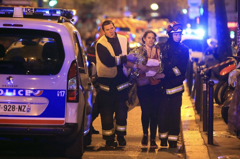 FILE - In this Nov. 13, 2015, file photo, rescue workers help a woman after an attack by Islamic State militants, outside the Bataclan theater in Paris. (AP Photo/Thibault Camus, File)