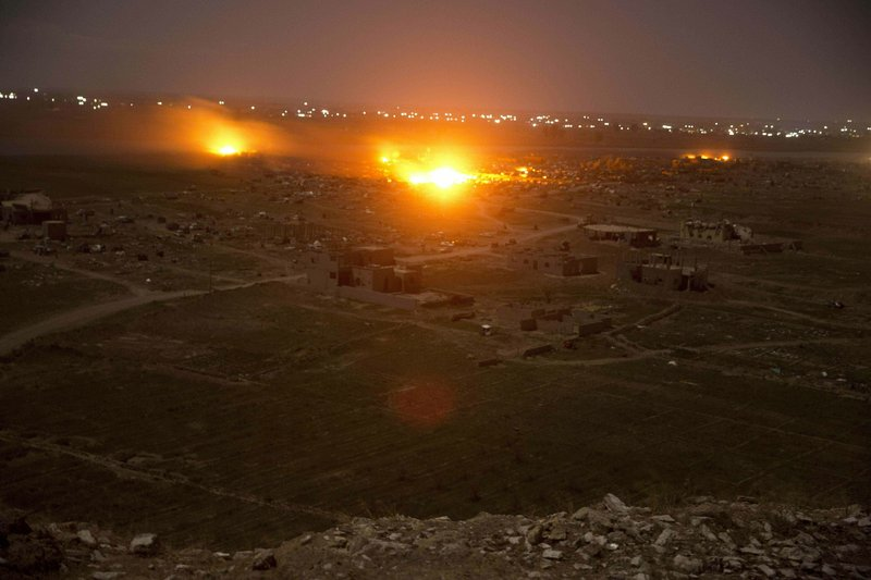 """FILE - In this March 18, 2019 file photo, Islamic State militant positions are ablaze in Baghouz, Syria as U.S-backed Syrian Democratic forces pound the group's remaining territory. In a video released on April 29, IS leader Abu Bakr al-Baghdadi extolled militants in Sri Lanka for """"striking the homes of the crusaders in their Easter, in vengeance for their brothers in Baghouz."""