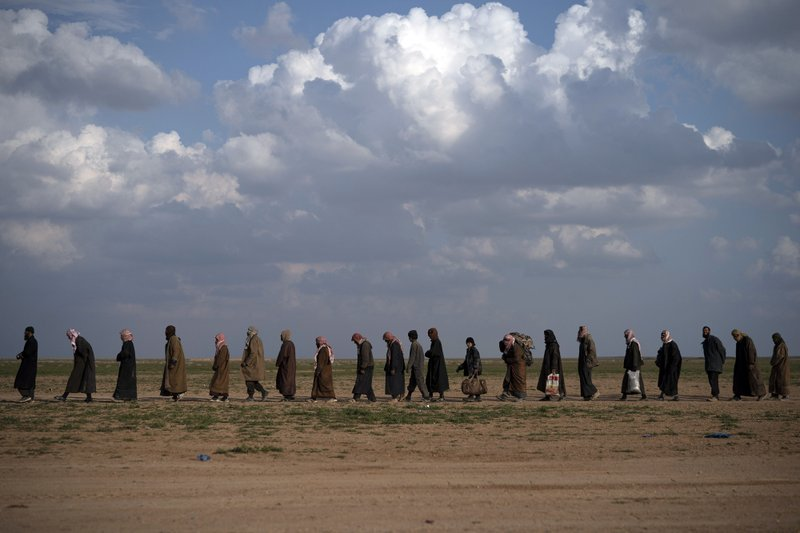 """FILE -  In this Feb. 22, 2019 file photo, men walk to be screened after being evacuated out of the last territory held by Islamic State militants, near Baghouz, eastern Syria. In a video released on April 29, IS leader Abu Bakr al-Baghdadi extolled militants in Sri Lanka for """"striking the homes of the crusaders in their Easter, in vengeance for their brothers in Baghouz."""