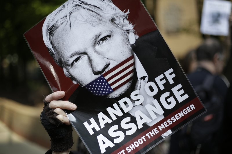 Protesters outside court as Julian Assange will appear to be sentenced on charges of jumping British bail seven years ago, in London, Wednesday May 1, 2019. Founder of WikiLeaks whistleblower site, Assange faces a separate court hearing later, on a U.S. extradition request, after being arrested at the Ecuadorian embassy April 11, when his political asylum was withdrawn.(AP Photo/Matt Dunham)