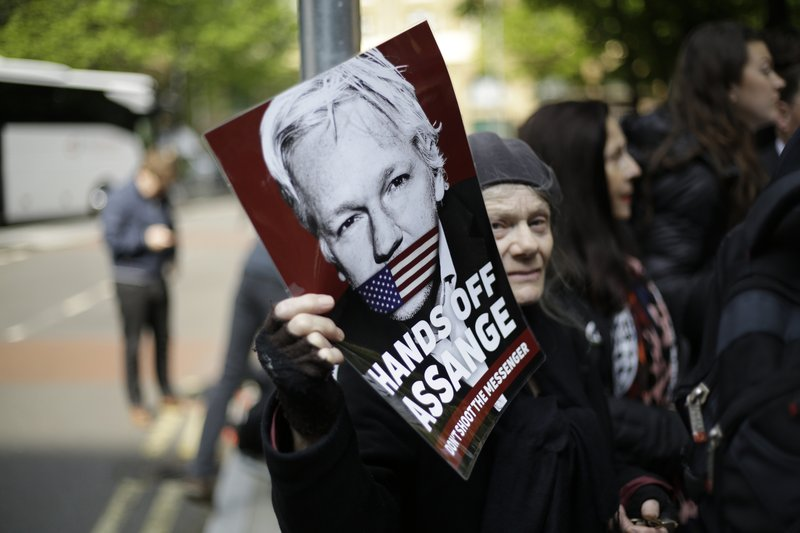 Protesters outside court as Julian Assange will appear to be sentenced on charges of jumping British bail seven years ago, in London, Wednesday May 1, 2019. Founder of WikiLeaks whistleblower site, Assange faces a separate court hearing later, on a U.S. extradition request, after being arrested at the Ecuadorian embassy April 11, after his political asylum was withdrawn. (AP Photo/Matt Dunham)