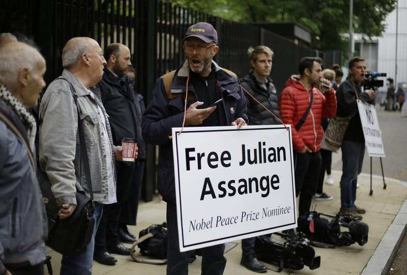 Protesters stand with media journalists outside court as Julian Assange is to appear at court to be sentenced on charges of jumping British bail seven years ago, in London, Wednesday May 1, 2019. Founder of WikiLeaks Assange was arrested at the Ecuadorian embassy April 11, after his political asylum was withdrawn. (AP Photo/Matt Dunham)