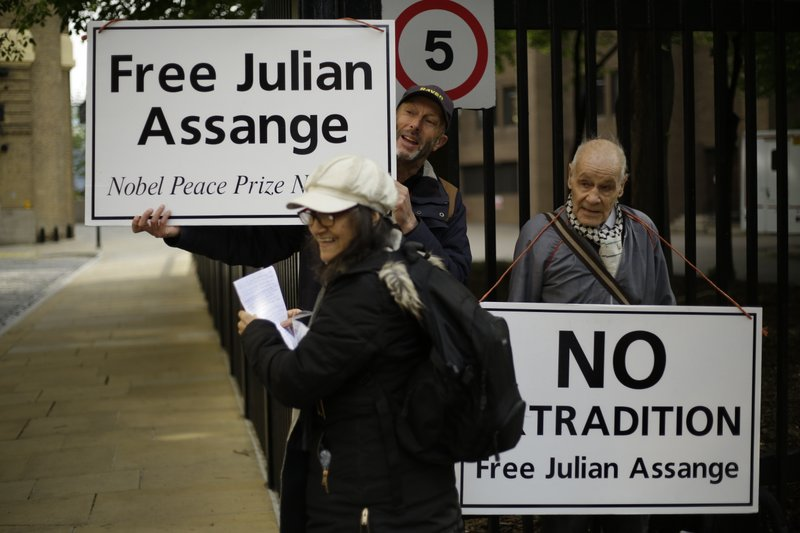 Protesters outside court as Julian Assange is to appear at court to be sentenced on charges of jumping British bail seven years ago, in London, Wednesday May 1, 2019. Founder of WikiLeaks Assange was arrested at the Ecuadorian embassy April 11, after his political asylum was withdrawn. (AP Photo/Matt Dunham)