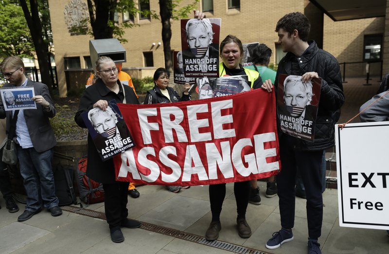 Protesters outside court as Julian Assange will appear to be sentenced on charges of jumping British bail seven years ago, in London, Wednesday May 1, 2019. Founder of WikiLeaks whistleblower website, Assange faces a separate court hearing later, on a U.S. extradition request, after being arrested at the Ecuadorian embassy April 11, when his political asylum was withdrawn. (AP Photo/Matt Dunham)