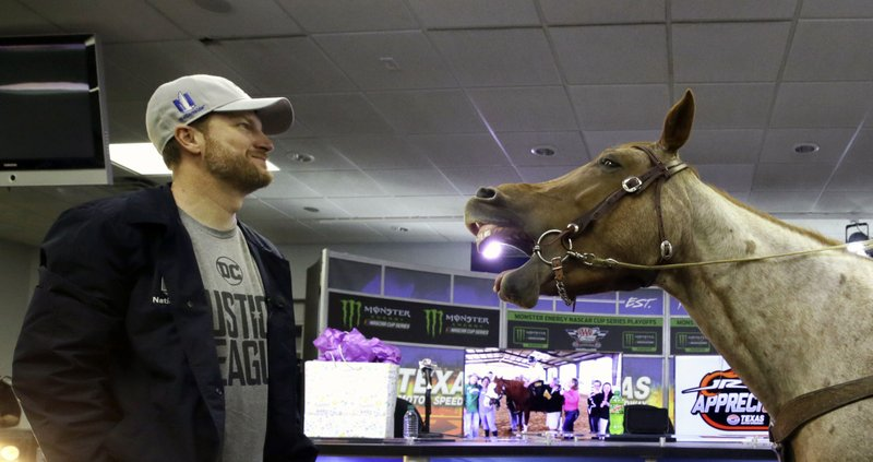 FILE - In this Nov. 3, 2017, file photo, Dale Earnhardt Jr., left, looks on as Eddie Gossage, president and CEO of Texas Motor Speedway, not shown, sits atop a horse during a presentation in the media center before a NASCAR Cup series auto race at Texas Motor Speedway in Fort Worth, Texas. Dale Earnhardt Jr. will work his first Kentucky Derby on Saturday, May 4, 2019, as part of his expanding role with NBC Sports. The retired NASCAR superstar is also slated to cover his first Indianapolis 500 later this month. (AP Photo/LM Otero, File)