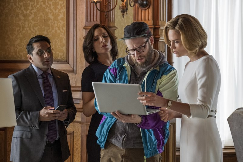 This image released by Lionsgate shows Ravi Patel, from left, June Diane Raphael, Seth Rogen and Charlize Theron in a scene from