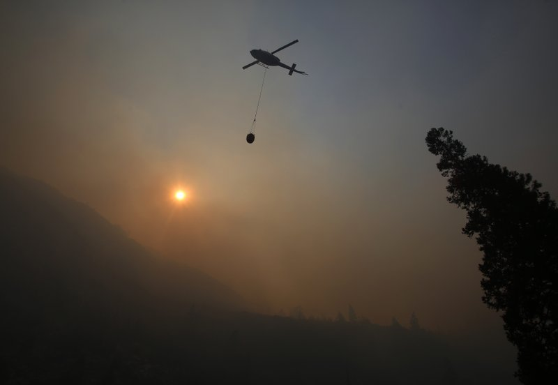 File - In this Aug. 14, 2018, file photo, a fire helicopter takes off through smoke rising to make a drop on active fires in Yosemite National Park, Calif. The National Interagency Fire Center is predicting a heavy wildfire season for areas along the west coast of the United States this summer. The Boise, Idaho-based center said Wednesday, May 1, 2019, that most of the country can expect a normal wildfire season in the period from May through August. (AP Photo/Gary Kazanjian, File)