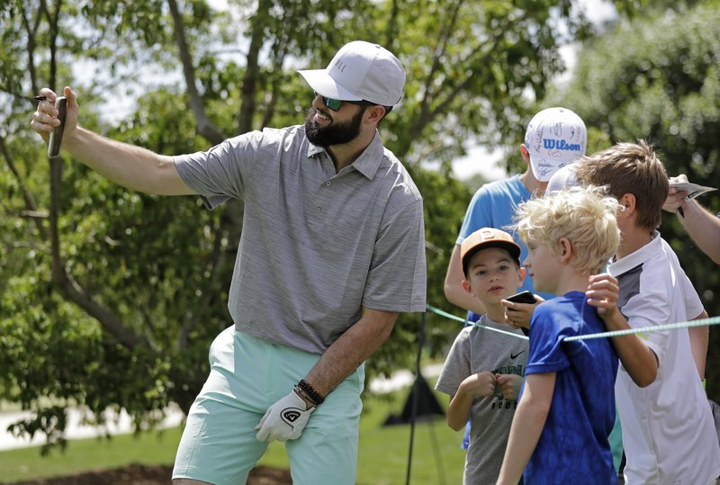 Carolina Panthers draft pick Will Grier takes a selfie with fans on the second hole during the pro-am of the Wells Fargo Championship golf tournament at Quail Hollow Club in Charlotte, N.C., Wednesday, May 1, 2019. Grier is kicking off his NFL career with the swagger of a starting NFL quarterback. The adulation surrounding the third-pick pick has created a buzz about the Panthers' QB situation with Cam Newton coming off shoulder surgery. (AP Photo/Chuck Burton)