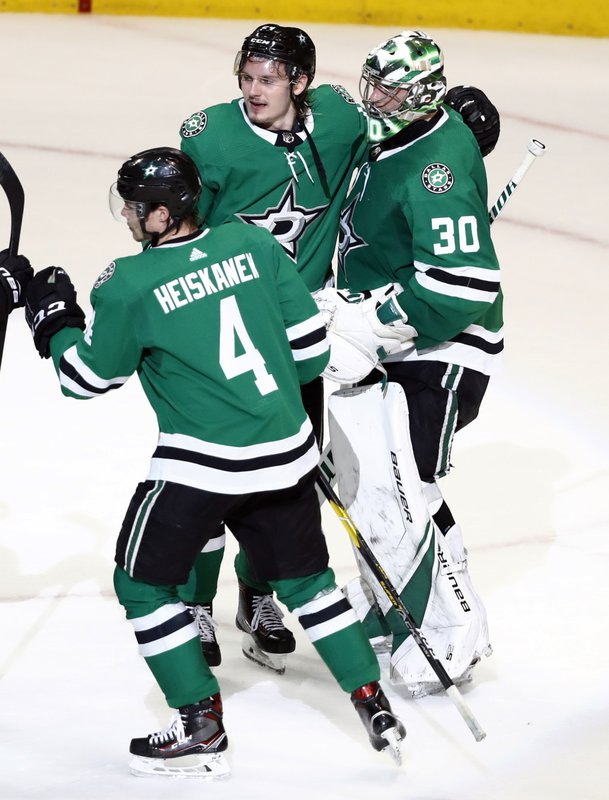 Dallas Stars goaltender Ben Bishop (30) celebrates with teammates Roope Hintz and Miro Heiskanen (4) after the Stars defeated the St. Louis Blues 4-2 in Game 4 of an NHL second-round hockey playoff series, Wednesday, May 1, 2019, in Dallas. (AP Photo/Tony Gutierrez)
