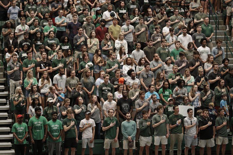 Students stand in Halton Arena during a vigil at the University of North Carolina-Charlotte in Charlotte, N.C., Wednesday, May 1, 2019 after a student with a pistol killed two people and wounded four others on Tuesday. (AP Photo/Chuck Burton)