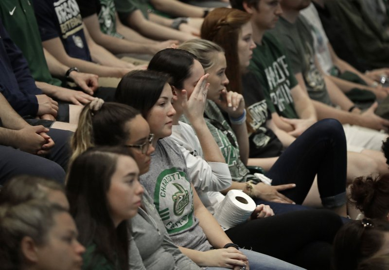 A student wipes her face during a vigil at the University of North Carolina-Charlotte in Charlotte, N.C., Wednesday, May 1, 2019 after a student with a pistol killed two people and wounded four others on Tuesday. (AP Photo/Chuck Burton)