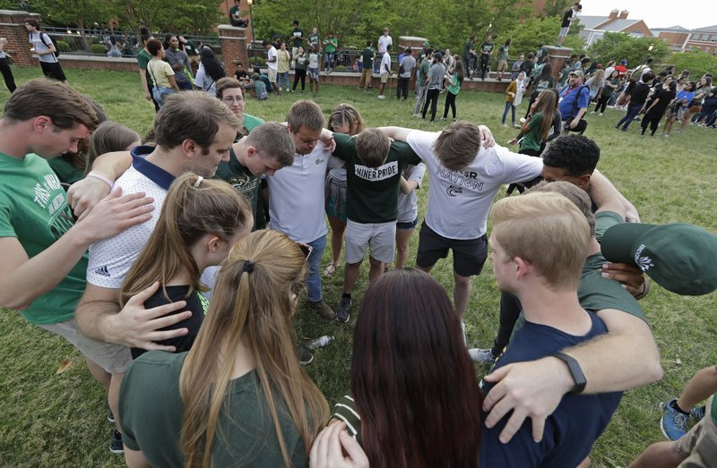 Students pray together during a vigil at the University of North Carolina-Charlotte in Charlotte, N.C., Wednesday, May 1, 2019 after a student with a pistol killed two people and wounded four others on Tuesday. (AP Photo/Chuck Burton)