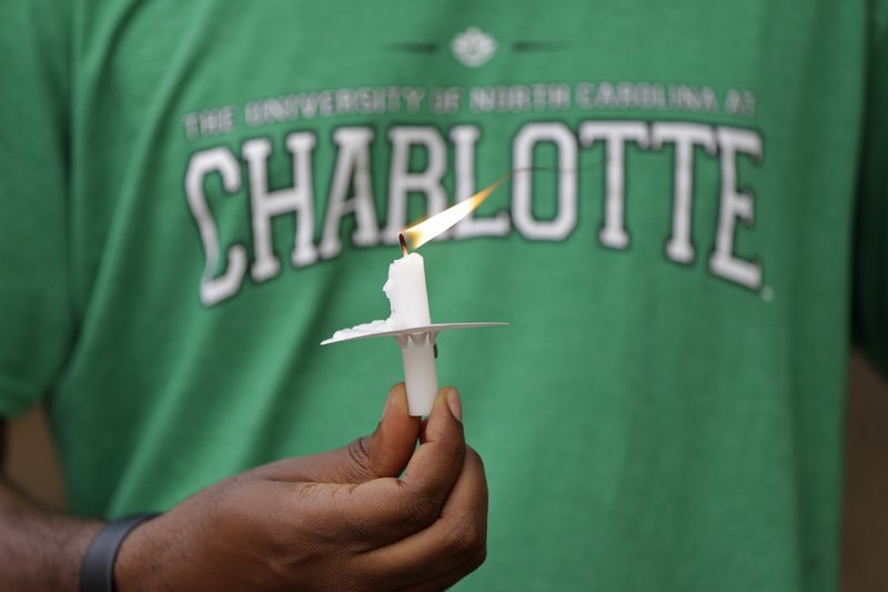A student holds a candle during a vigil at the University of North Carolina-Charlotte in Charlotte, N.C., Wednesday, May 1, 2019 after a student with a pistol killed two people and wounded four others on Tuesday. (AP Photo/Chuck Burton)