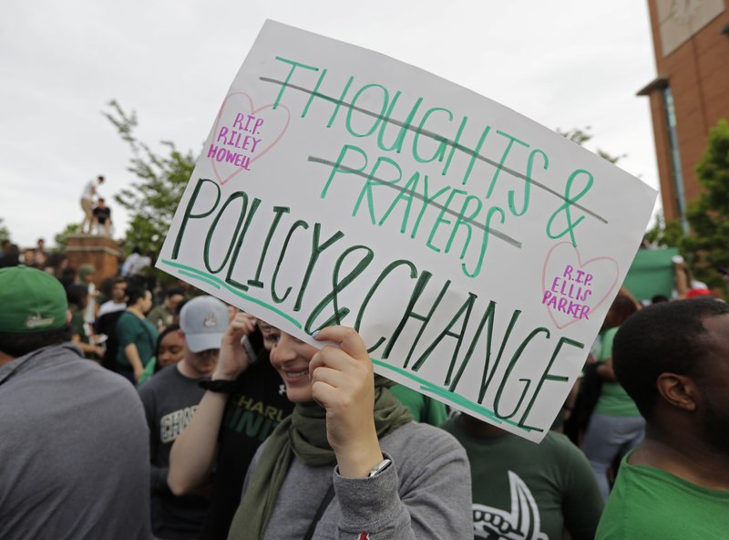 A student carries a sign as she leaves a vigil at the University of North Carolina-Charlotte in Charlotte, N.C., Wednesday, May 1, 2019 after a student with a pistol killed two people and wounded four others on Tuesday. (AP Photo/Chuck Burton)