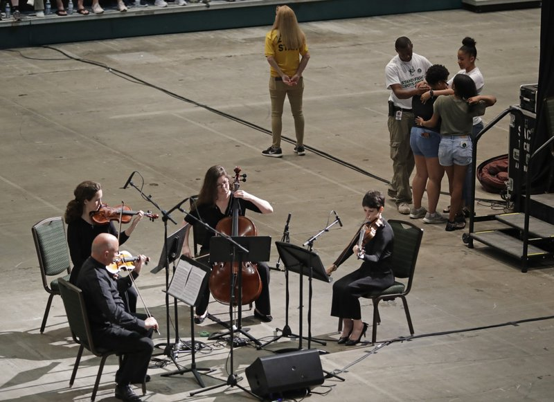 Students hug as musicians play before a vigil at the University of North Carolina-Charlotte in Charlotte, N.C., Wednesday, May 1, 2019 after a student with a pistol killed two people and wounded four others on Tuesday. (AP Photo/Chuck Burton)