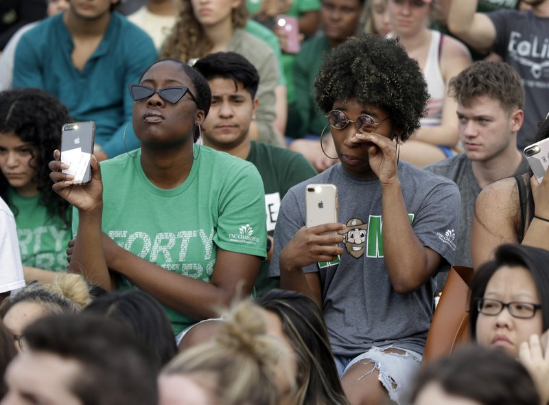 A student wipes her face as she holds her phone flashlight during a vigil at the University of North Carolina-Charlotte in Charlotte, N.C., Wednesday, May 1, 2019 after a student with a pistol killed two people and wounded four others on Tuesday. (AP Photo/Chuck Burton)