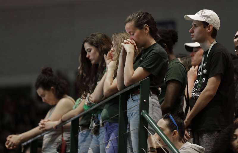 Students observer a moment of silence during a vigil at the University of North Carolina-Charlotte in Charlotte, N.C., Wednesday, May 1, 2019 after a student with a pistol killed two people and wounded four others on Tuesday. (AP Photo/Chuck Burton)