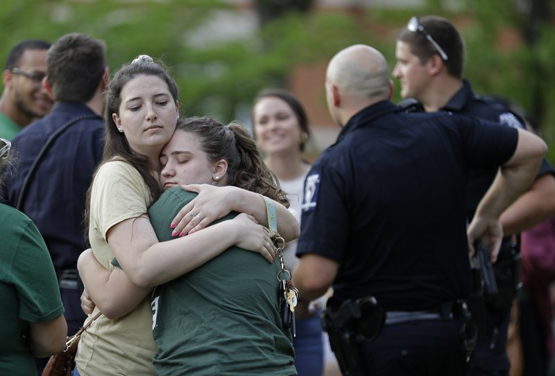 Two students hug during a vigil at the University of North Carolina-Charlotte in Charlotte, N.C., Wednesday, May 1, 2019 after a student with a pistol killed two people and wounded four others on Tuesday. (AP Photo/Chuck Burton)