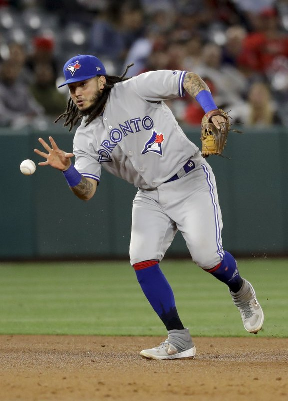 Toronto Blue Jays shortstop Freddy Galvis bare-hands a ball hit by Los Angeles Angels' Jonathan Lucroy during the fifth inning of a baseball game in Anaheim, Calif., Wednesday, May 1, 2019. Lucroy was out at first. (AP Photo/Chris Carlson)