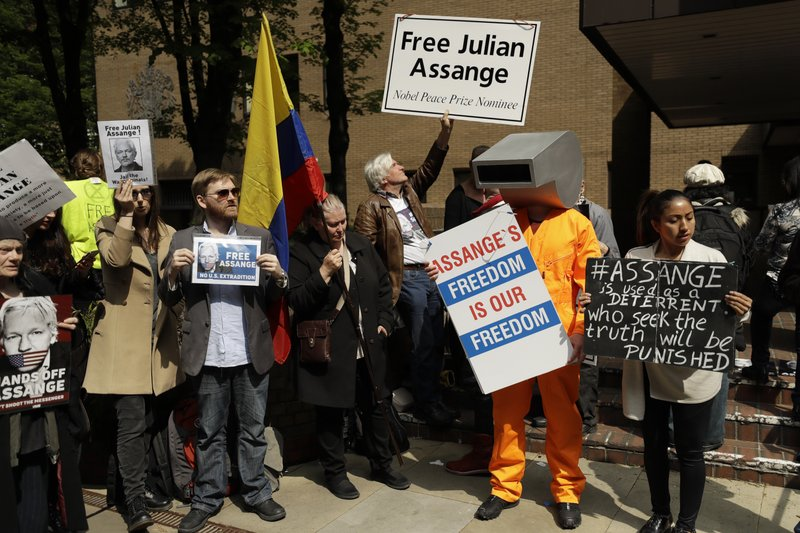 Protesters outside court as Julian Assange will appear to be sentenced on charges of jumping British bail seven years ago, in London, Wednesday May 1, 2019. Founder of WikiLeaks whistleblower website, Assange faces a separate court hearing on a U.S. extradition request, after being arrested at the Ecuadorian embassy April 11, when his political asylum was withdrawn.(AP Photo/Matt Dunham)