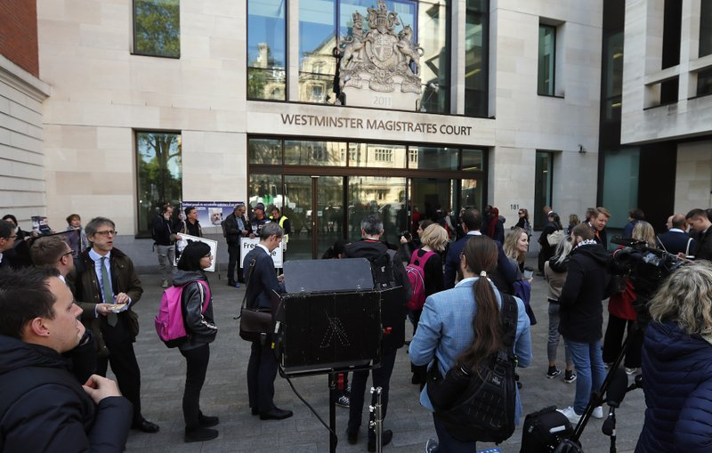 Media and supporters wait at the entrance to Westminster Magistrates Court in London, Thursday, May 2, 2019, where WikiLeaks founder Julian Assange is expected to appear by video link from prison.  Assange is facing a court hearing over a U.S. request to extradite him for alleged computer hacking.(AP Photo/Frank Augstein)