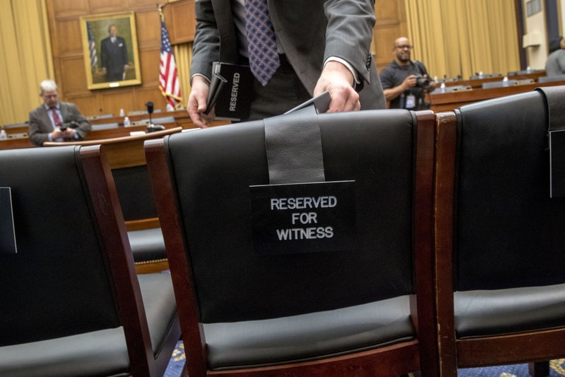 A congressional aide puts out placards for aides to Attorney General William Barr who is not expected to appear before a House Judiciary Committee hearing on Capitol Hill in Washington, Thursday, May 2, 2019. The House Judiciary Committee witness chair will be without its witness this morning, Attorney General William Barr, who informed the Democrat-controlled panel he will skip a scheduled hearing on special counsel Robert Mueller's report, escalating an already acrimonious battle between Democrats and the Justice Department. (AP Photo/Andrew Harnik)