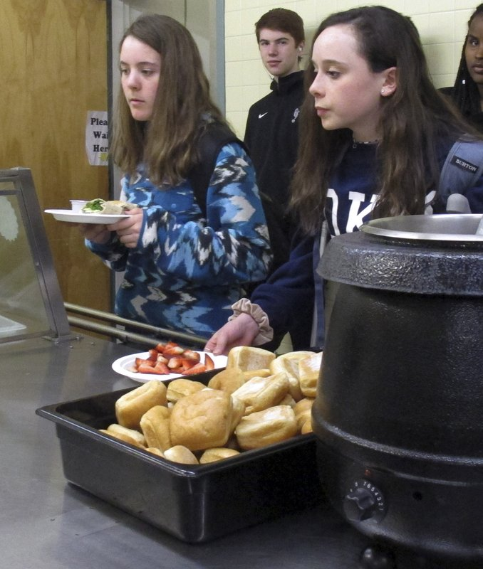 In this Friday, April 5, 2019 photo, students wait in line for lunch at Burlington High School, in Burlington, Vt. The school's food service provider is preparing to comply with a Trump administration decision to roll back a rule that required only whole-grain rich foods for school meals. Burlington officials said they don't plan on abandoning whole-grain foods, but it gives them flexibility. (AP Photo/Wilson Ring)