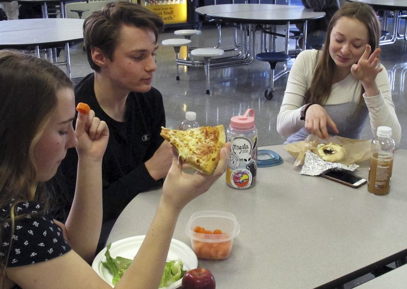 In this Friday, April 5, 2019 photo, Burlington High School student Emma McCobb, left, holds a piece of pizza while eating with classmates in the school cafeteria in Burlington, Vt. The school's food service provider is preparing to comply with a Trump administration decision to roll back a rule that required only whole-grain rich foods for school meals. Burlington officials said they don't plan on abandoning whole-grain foods, but it gives them flexibility. (AP Photo/Wilson Ring)