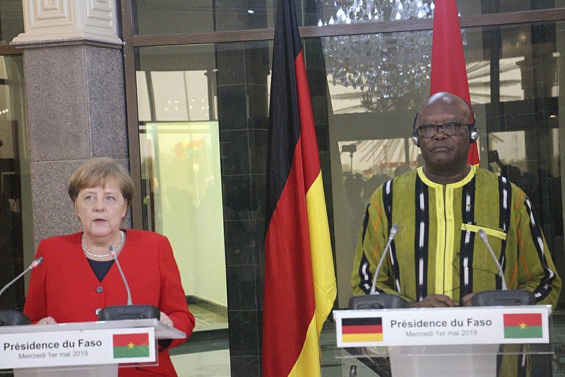 German Chancellor Angela Merkel, left, speaks during a news conference while Burkina Faso President, Roch Marc Christian Kabore, right, listens at the Presidential Palace in Ouagadougou, Burkina Faso, Wednesday, May 1, 2019. Merkel has arrived in the West African nation of Burkina Faso. Merkel is on a three-nation tour in the region. (AP Photo/Alain Didier Compaore)