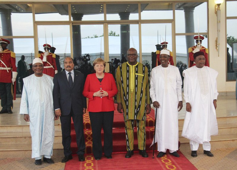 German Chancellor Angela Merkel, center, poses for a photograph at the end of the G-5 Sahel summit between the presidents of Burkina Faso, Mali, Chad, Mauritania and Niger at the Presidential Palace in Ouagadougou, Burkina Faso, Wednesday, May 1, 2019. Merkel has arrived in the West African nation of Burkina Faso. Merkel is on a three-nation tour in the region. (AP Photo/Alain Didier Compaore)