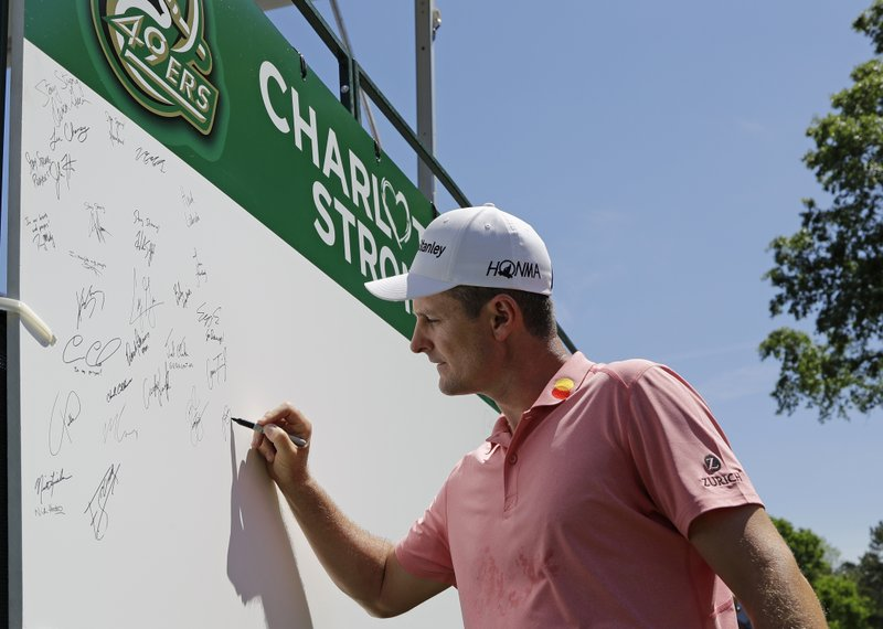 Justin Rose, of England, signs a board on the first tee in support of the victims of the shooting at the University of North Carolina-Charlotte during the first round of the Wells Fargo Championship golf tournament at Quail Hollow Club in Charlotte, N.C., Thursday, May 2, 2019. (AP Photo/Chuck Burton)