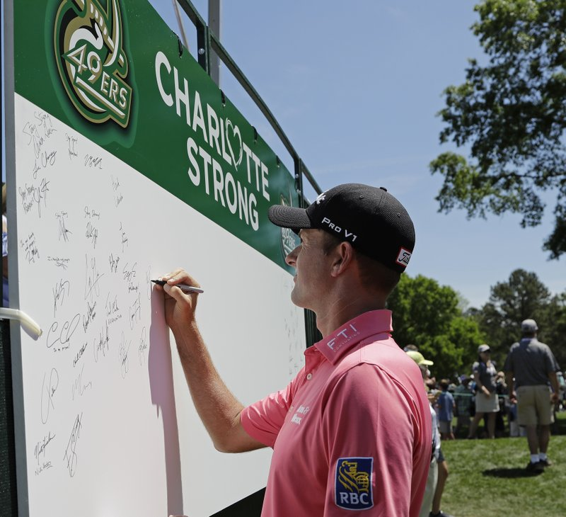Webb Simpson signs a board on the first tee in support of the victims of the shooting at the University of North Carolina-Charlotte during the first round of the Wells Fargo Championship golf tournament at Quail Hollow Club in Charlotte, N.C., Thursday, May 2, 2019. (AP Photo/Chuck Burton)