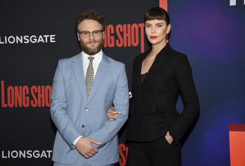Actors Seth Rogen, left, and Charlize Theron pose together at the premiere of