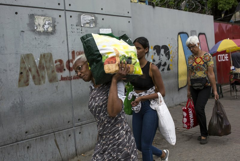 Women carry their purchases they bought at the the Coche Market in Caracas, Venezuela, Thursday, May 2, 2019. The bustling Coche Market is a sign that Caracas has returned to life after the recent outburst of violent unrest. (AP Photo/Rodrigo Abd)