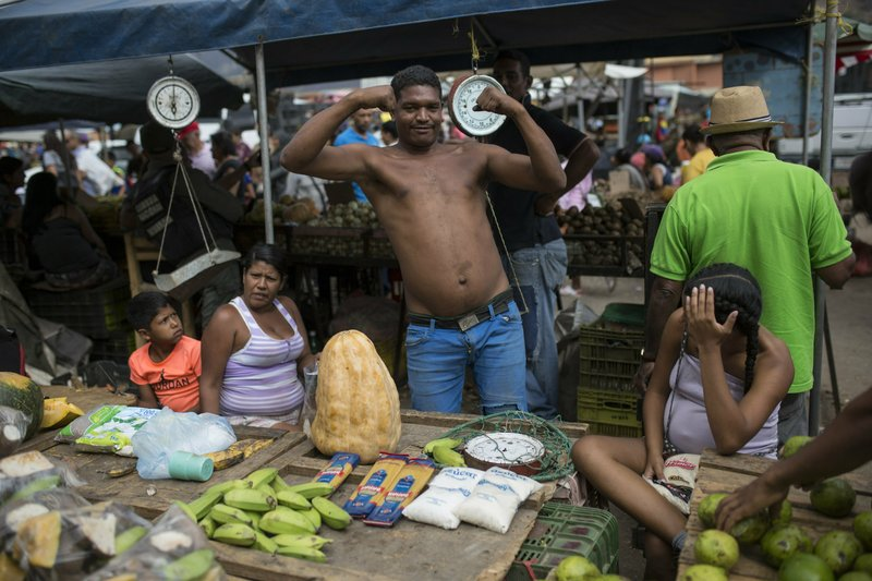 A vendor stikes a pos at the Coche Market in Caracas, Venezuela, Thursday, May 2, 2019.  A return to political calm gave way to bustling life at the open-air market tucked below a hillside barrio in one corner of the capital. (AP Photo/Rodrigo Abd)
