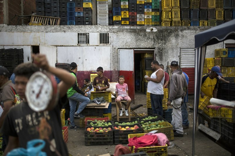 Vendors wait for customers at the Coche Market in Caracas, Venezuela, Thursday, May 2, 2019. In its narrow pathways, bare chested workers push carts heavy with sacks of onions and potatoes, vying for space with shoppers and vendors selling cigarettes and bottled water. (AP Photo/Rodrigo Abd)