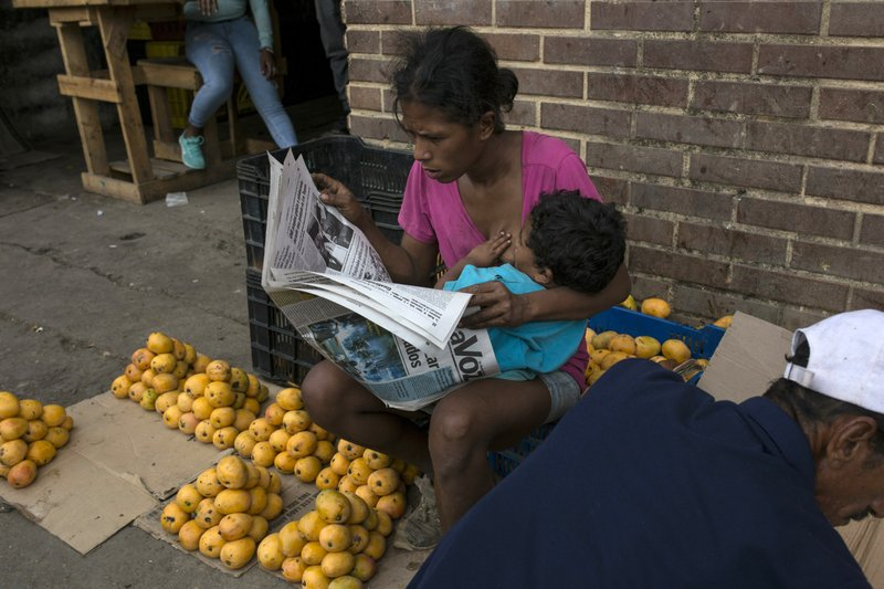 A mango vendor breastfeeds her son as she reads a newspaper while waiting for customers at the Coche Market in Caracas, Venezuela, Thursday, May 2, 2019. A return to political calm gave way to bustling life of the open-air market tucked below a hillside barrio in one corner of the capital. (AP Photo/Rodrigo Abd)