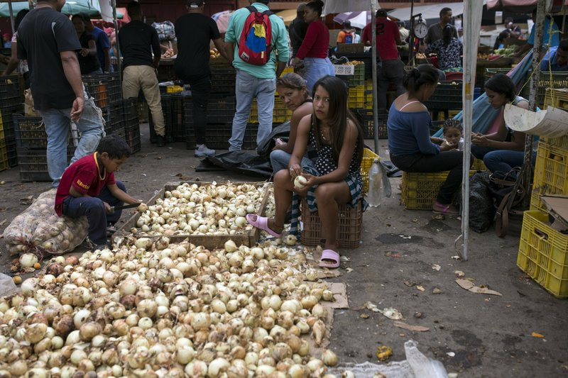 Vendors clean onions at the Coche Market in Caracas, Venezuela, Thursday, May 2, 2019. Farmers truck in the produce, meat and coffee from miles around the capital to the market known for its low prices. Its customers include everybody from restaurant owners to homemakers. (AP Photo/Rodrigo Abd)