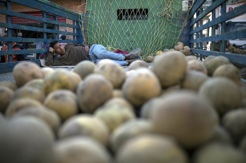 Sixteen-year-old Daiver Chorines rests after working all night selling melons at the Coche Market in Caracas, Venezuela, Thursday, May 2, 2019. Farmers truck in the produce, meat and coffee from miles around the capital to the market known for its low prices. Its customers include everybody from restaurant owners to homemakers. (AP Photo/Rodrigo Abd)